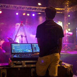 Sound engineer team working to prepare for music concert stage. Hand adjusting audio mixer. DJ for work at a concert in front of the stages.